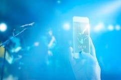 音乐迷采取阶段的一个照片吉他弹奏者在智能手机、淡色口气和软的焦点的音乐会 免版税库存照片