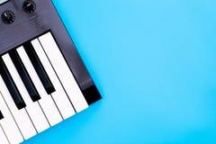 音乐键盘在蓝色拷贝空间的合成器仪器 库存图片