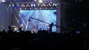 音乐音乐会的人群人 在明亮的五颜六色的阶段光前面的欢呼的生活方式人群 剪影  影视素材