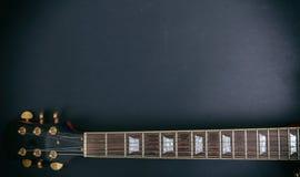 音乐,吉他 一个吉他脖子fretboard和床头柜的顶视图反对黑背景 库存照片