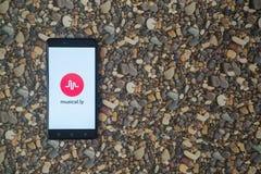 音乐 在智能手机的ly商标在小石头背景  免版税库存图片