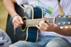 音响弹蓝色声学吉他的吉他弹奏者年轻人 免版税库存图片