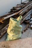 页被编织的工业大袋建筑沙子袋子请求和木wast 图库摄影