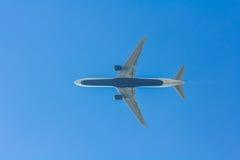 顶上喷气式客机航空器的飞行的下面 免版税库存图片
