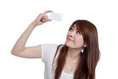 顶上的卡片查寻并且微笑的亚洲女孩展示 免版税库存图片