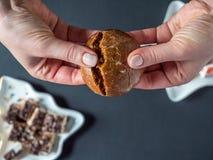 顶上的在黑暗的背景的看法女性手断裂圣诞节德国黑暗的巧克力Lebkuchen蛋糕 免版税图库摄影