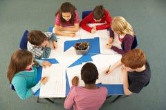 顶上的学童一起查看工作 免版税图库摄影