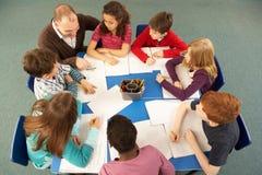 顶上的学童一起查看工作 免版税库存照片