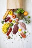 顶上的看法、白色木表面上的纸袋不同的水果和蔬菜 健康食品背景,顶视图 ?? 免版税库存图片