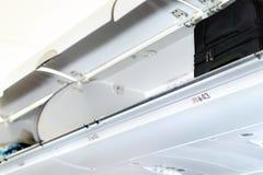 顶上的衣物柜和隔间行李的在飞机 免版税库存照片