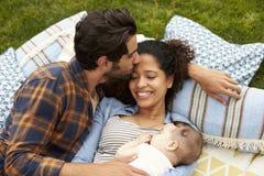 顶上的观点的与放松在地毯的婴孩的家庭在庭院里 免版税图库摄影