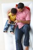 顶上的观点的父亲和儿子沙发的使用数字式片剂 库存图片