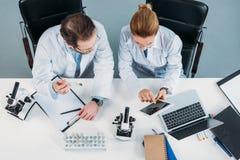 顶上的观点的白色外套的科学研究员使用片剂一起在工作场所 免版税图库摄影