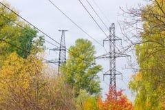 顶上的输电线传输塔反对秋天叶片的 库存图片
