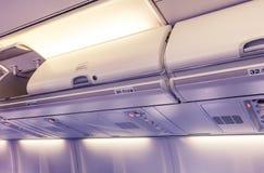 顶上的隔间-飞机客舱内部的细节在紫罗兰和黄色定了调子 免版税库存图片
