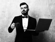 顶头经理早晨 有微笑的面孔表示的CEO拿着杯子饮料和膝上型计算机在手上,在米黄葡萄酒墙壁上 免版税库存图片