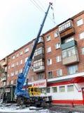 顶房顶修理一个五层砖家与一台起重机在市鄂木斯克 库存图片