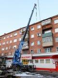 顶房顶修理一个五层砖家与一台起重机在市鄂木斯克 免版税库存图片