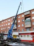 顶房顶修理一个五层砖家与起重机 库存照片