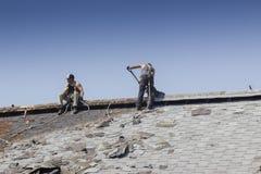 顶房顶谷仓的建筑工人 图库摄影