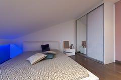 顶楼公寓的-在突出a的低灯的射击卧室 库存图片