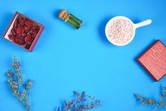 顶视图、瓶被安置的,空白的标签包裹嘲笑的在蓝色背景和花 免版税库存照片