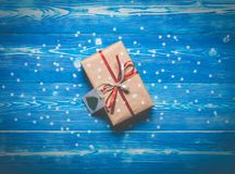 顶视图与一条红色丝带的圣诞节礼物在与雪花的蓝色背景 免版税库存照片