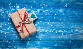 顶视图与一条红色丝带的圣诞节礼物在与雪花的蓝色背景 图库摄影