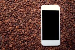 顶视图与智能手机的咖啡豆 库存图片