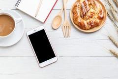 顶视图丹麦酥皮点心、咖啡、笔记本和智能手机在wh 库存照片