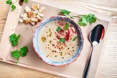 顶视图为与jamon,荷兰芹的奶油色汤服务,并且面包wooen背景 午餐的平的被放置的食物 r 库存图片
