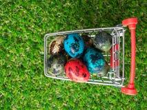 顶视图五颜六色在红色购物车的多复活节彩蛋在绿草 库存照片