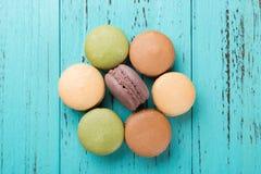 顶视图五颜六色的蛋白杏仁饼干演播室射击塑造了象在蓝色木头的一朵花 库存图片
