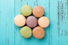 顶视图五颜六色的蛋白杏仁饼干演播室射击塑造了象在蓝色木头的一朵花 库存照片