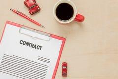 顶视图企业与咖啡汽车笔的合同形式 免版税库存图片