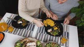 顶视图作为丈夫和妻子的家庭晚餐在桌上在厨房里 在桌上是沙拉、玉米和绿豆 影视素材