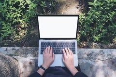 顶视图使用和键入在有空白的白色屏幕的膝上型计算机的妇女的大模型图象,坐在室外与自然 免版税库存照片