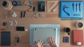 顶视图使用他的膝上型计算机cimputer的技术员工程师键入,但是不工作,并且他在他的书桌上修理 股票录像