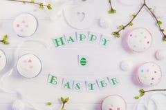 顶视图假日结构的愉快的复活节字法,与绿叶年轻射击的分支,装饰了杯形蛋糕, merengue甜点 库存图片