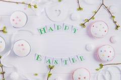 顶视图假日结构的愉快的复活节字法,与绿叶年轻射击的分支,装饰了杯形蛋糕, merengue甜点 免版税库存图片