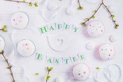 顶视图假日结构的愉快的复活节字法,与绿叶年轻射击的分支,装饰了杯形蛋糕, merengue甜点 图库摄影