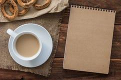 顶视图办公室工作场所:Ð ¡ ardboard笔记薄用百吉卷和咖啡在木桌上 免版税库存照片