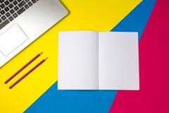顶视图办公室桌书桌 与膝上型计算机和开放笔记本的工作区有在五颜六色的背景的紫罗兰色铅笔的 库存照片