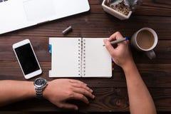 顶视图办公桌大模型:膝上型计算机、笔记本、智能手机、笔、花和咖啡 库存图片