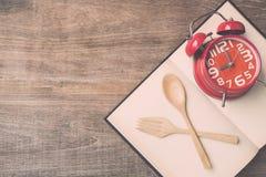 顶视图匙子、叉子、书和红色时钟在木板条backgro 图库摄影