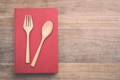 顶视图匙子、叉子和书在木板条背景 库存图片