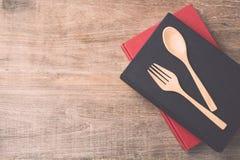 顶视图匙子、叉子和书在木板条背景 库存照片