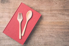 顶视图匙子、叉子和书在木板条背景 免版税图库摄影