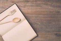 顶视图匙子、叉子和书在木板条背景 图库摄影