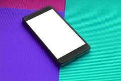 顶视图反对时髦多色背景的大模型智能手机 免版税图库摄影